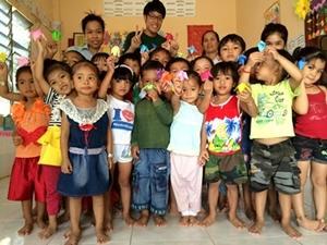 Un grupo de niños junto a voluntarios de Projects Abroad, posando con origamis hechos en la clase, en un Centro de Cuidado en Camboya.