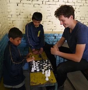 Projects Abroad teaching volunteer plays chess with two Nepalese boys at Deepmala's English camp during the school break.
