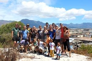Forografía grupal de voluntarios de Projects Abroad y niños locales con las montañas y una población desfavorecida de fondo.