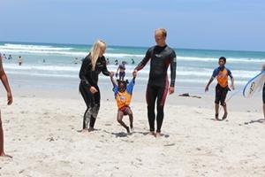 Niña sudafricana jugando con dos voluntarios del Proyecto de Surf en la playa de Muizenberg en Ciudad del Cabo.