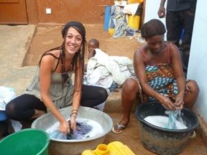 Volunteer helps local women wash dishes at a project in Togo