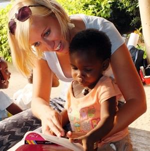 Female volunteer helping a child to read in Togo