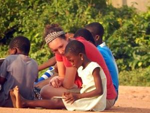 Niños ghaneses escuchan a una voluntaria leyendo una historia en un campo de fútbol