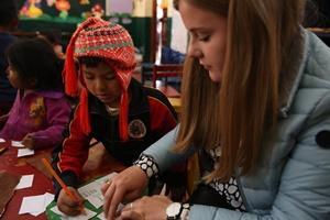 Un niño y una voluntaria en Perú hacen manualidades en un centro infantil