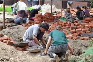 Una pareja de voluntarios excava zanjas para construir escuelas en Nepal
