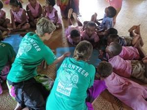 Niños de jardín infantil en una actividad creativa ayudados por voluntarios en Fiyi