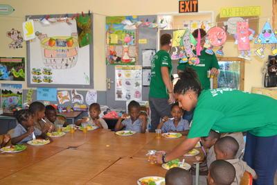 Voluntarios sirviendo una comida nutritiva a niños en proyecto de Trabajo Social en Jamaica