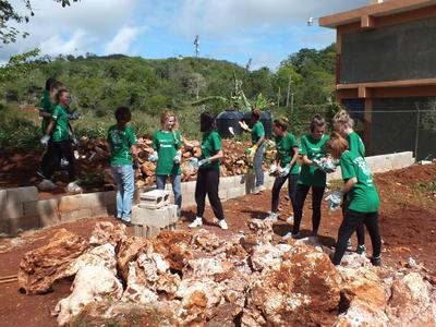 Voluntarios de construcción despejando terreno para patio de juegos en Jamaica