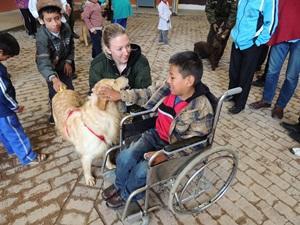 Un niño discapacitado junto a una voluntaria de Projects Abroad y un perro en Bolivia