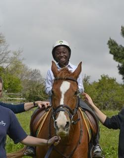Un niño local participa de una sesión de Equinoterapia junto a Projects Abroad en Sudáfrica