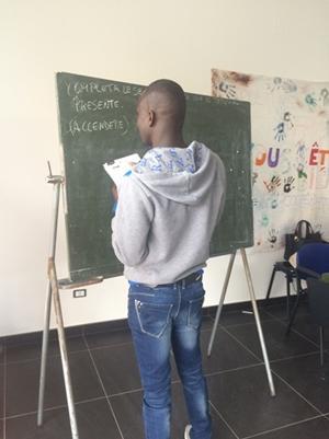 Un refugiado tomando nota de lo aprendido en una clase en el proyecto de Ayuda a los Refugiados en Italia