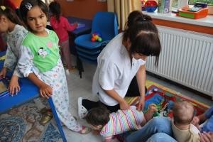 Voluntaria y bebés en sala de juegos en Rumanía