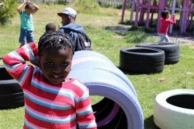 Una niña de una zona desfavorecida en Sudáfrica sonrie para la cámara