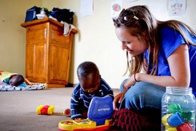 Una voluntaria juega con un niño sudafricano en un centro de cuidado en Sudáfrica