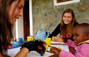 Voluntarias y niña en actividad con títeres en Tanzania