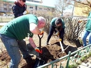 A group of Grown-up Special volunteers work together on a community project.