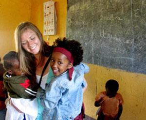 Voluntaria y niños en centro de cuidado durante proyecto Comunitario para adolescentes en Tanzania