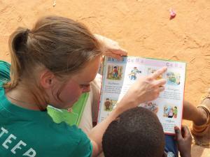 Voluntaria de Projects Abroad lee a un niño en Lomé.