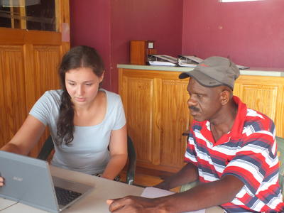 Voluntaria en Jamaica le muestra a un local el programa de manejo de desastres