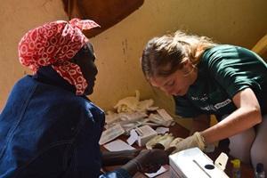 Una mujer local recibe tratamiento de una voluntaria del proyecto de Medicina de Projects Abroad en África.