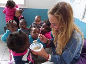 Voluntaria de Projects Abroad alimentando a niños en el Proyecto de Nutrición en Sudáfrica
