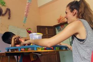 Una voluntaria realiza juegos terapéuticos con un niño discapacitado en el proyecto de Terapia Ocupacional en Camboya