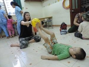 A Vietnamese child receives physical therapy treatment from an intern