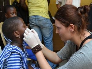 A local child is helped by a female volunteer in Ghana, Africa.