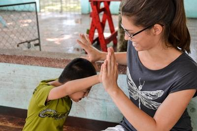 Voluntaria del proyecto de Terapia del Hablade Projects Abroad trabaja jugando con un niños vitnamita en un centro de rehabilitación en Asia.