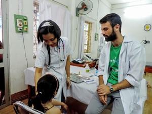Un interno examina a un niño junto a un voluntario en un centro médico en Vietnam