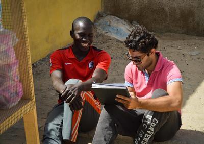 Pasante de microfinanzas revisa plan de negocios con beneficiario en Senegal