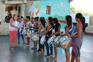 Voluntaria enseñando a niños a tocar el tambor en el proyecto de Artes Creativas en Ecuador