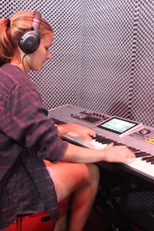 Una voluntaria de Projects Abroad trabaja en el estudio, grabando música que toca en el teclado en Sudáfrica.