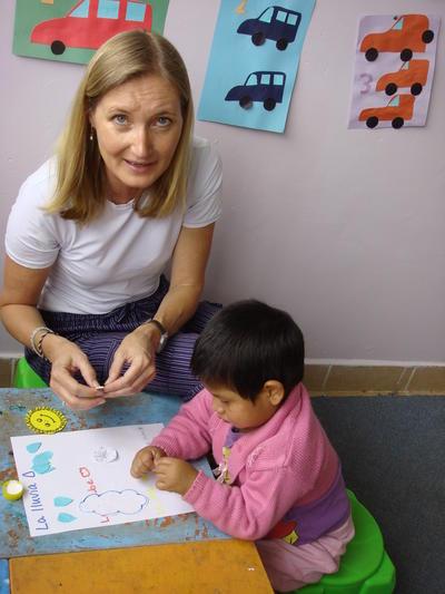 Niño completando actividad con ayuda de trabajadora social voluntaria en Bolivia