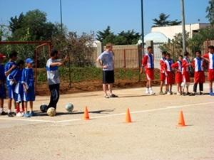 Moroccan children participate in soccer drills at a practice coached by a volunteer.