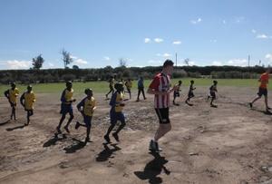 Dos voluntarios de Projects Abroad con niños de la escuela de Kenia realizando ejercicio de pre-calentamiento antes de la práctica de fútbol.