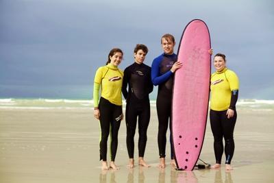 Dos estudiantes junto a sus profesores voluntarios de surf