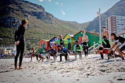 Un voluntario prepara a los niños para su lección de surf en Sudáfrica
