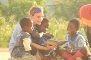 Niños escuchan atentamente a una voluntaria leyendo un cuento en Ghana