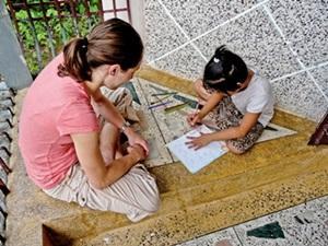 Una voluntaria de Projects Abroad acompaña a una niña de Nepal mientras dibuja en el Proyecto de Enseñanza