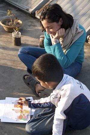 Una voluntaria de Projects Abroad lee junto a un niño nepalí en el Proyecto de Enseñanza