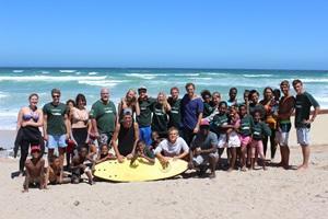 Voluntarios de Projects Abroad y niños sudafricanos disfrutan la playa en Muizenberg, Ciudad del Cabo.